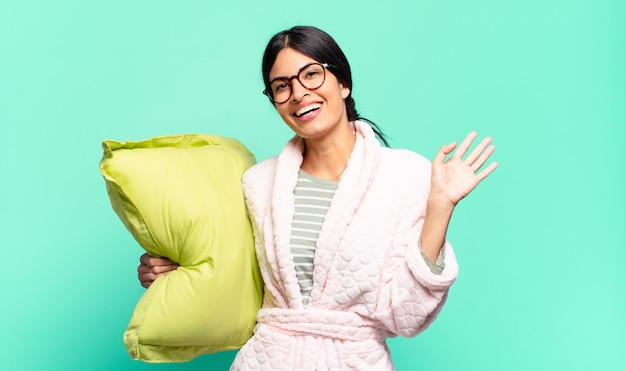 Jeune jolie femme souriant joyeusement et gaiement, agitant la main, vous accueillant et vous saluant, ou vous disant au revoir. concept de pyjama