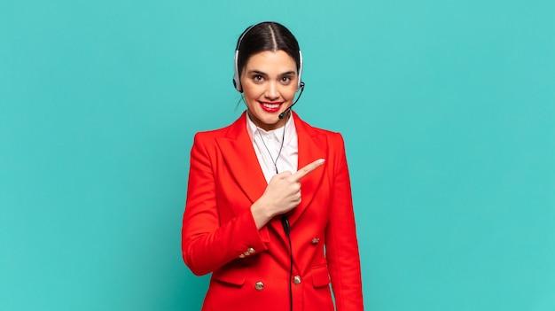 Jeune jolie femme souriant joyeusement, se sentant heureuse et pointant vers le côté et vers le haut, montrant l'objet dans l'espace de copie. concept de télévendeur