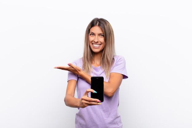 Jeune jolie femme souriant joyeusement, se sentant heureux et montrant un concept dans l'espace de copie avec la paume de la main tenant un téléphone intelligent