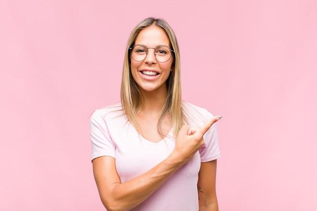 Jeune jolie femme souriant joyeusement, se sentant heureux et pointant vers le côté et vers le haut, montrant l'objet dans l'espace de copie