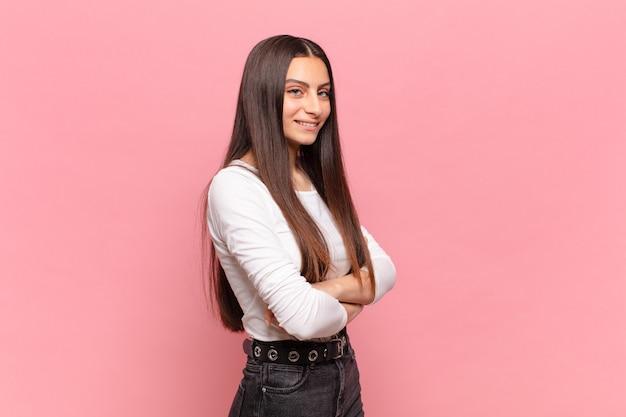 Jeune jolie femme souriante à la caméra avec les bras croisés et une expression heureuse, confiante et satisfaite