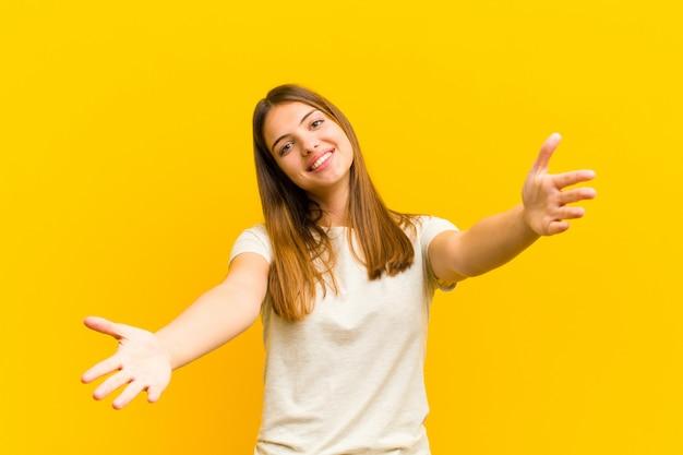 Jeune jolie femme souriante donnant joyeusement un câlin de bienvenue chaleureux, amical et affectueux, se sentant heureux et adorable sur le mur orange