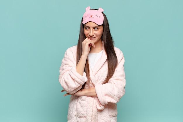 Jeune jolie femme souriante avec une expression heureuse et confiante avec la main sur le menton, se demandant et regardant sur le côté. concept de réveil en pyjama
