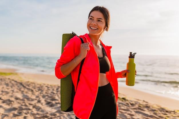 Jeune jolie femme souriante, faire du sport au lever du soleil du matin sur la plage de la mer tenant un tapis de yoga et une bouteille d'eau, mode de vie sain, écouter de la musique sur les écouteurs, porter une veste coupe-vent rose