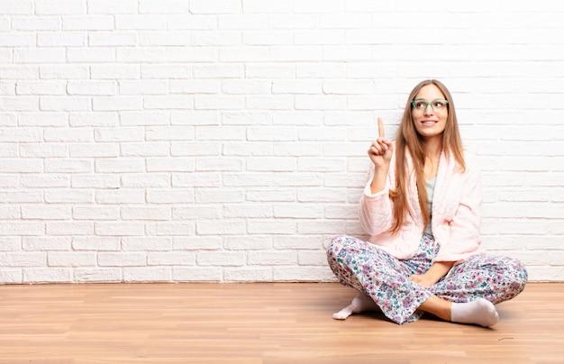Jeune jolie femme souriante gaie et joyeuse, pointant vers le haut avec une main pour copier l'espace. concept de maison