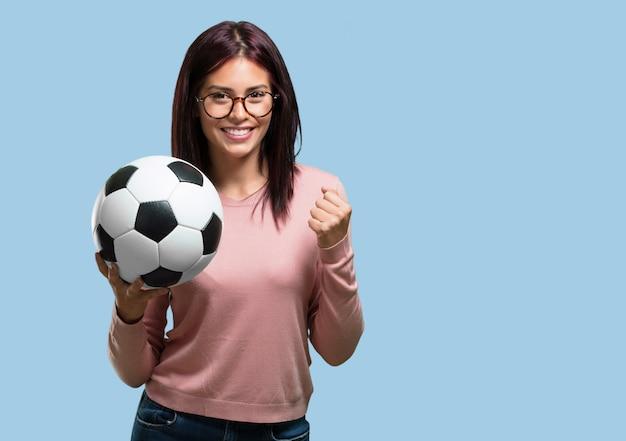 Jeune jolie femme souriante et heureuse, tenant un ballon de foot, attitude compétitive