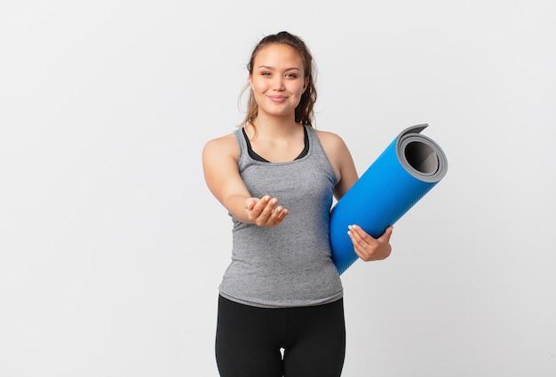 Jeune jolie femme souriante joyeusement avec amicale et offrant et montrant un concept et tenant un tapis de yoga