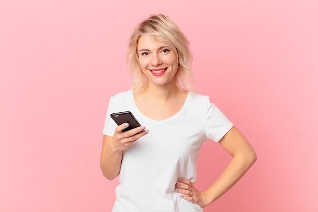Jeune jolie femme souriante joyeusement avec une main sur la hanche et confiante. notion de cellule