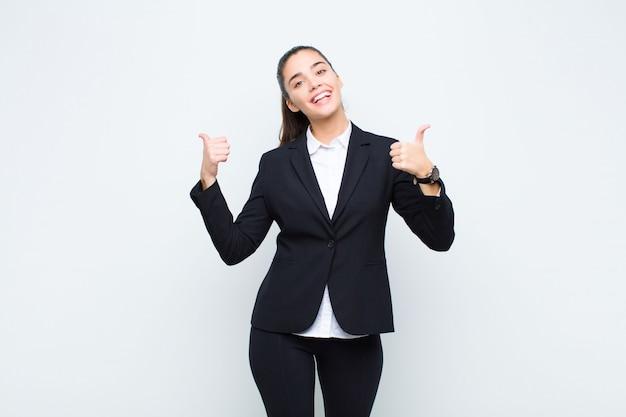 Jeune jolie femme souriante joyeusement et à la recherche de bonheur, se sentir insouciant et positif avec les deux pouces vers le haut du concept d'entreprise