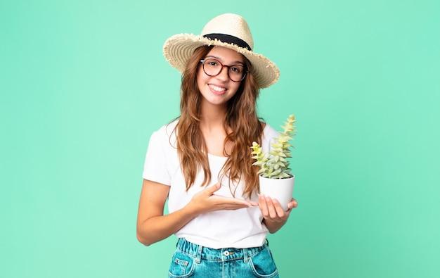 Jeune Jolie Femme Souriante Joyeusement, Se Sentant Heureuse Et Montrant Un Concept Avec Un Chapeau De Paille Et Tenant Un Cactus Photo Premium