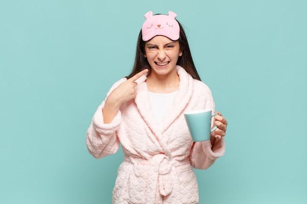 Jeune jolie femme souriante pointant avec confiance vers son propre large sourire, attitude positive, détendue et satisfaite. concept de réveil en pyjama