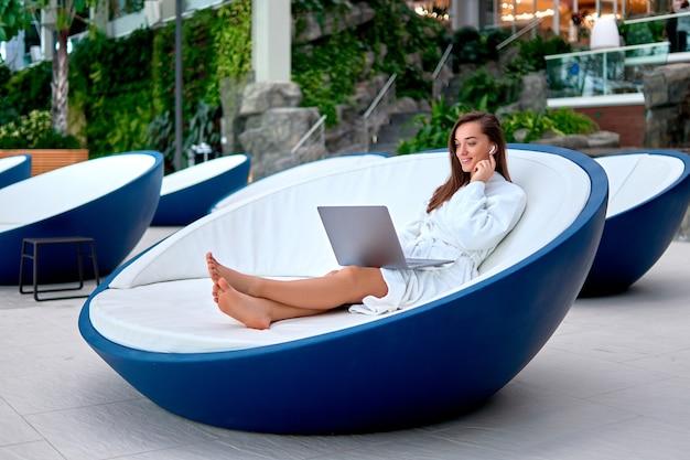 Jeune jolie femme souriante portant un peignoir blanc à l'aide d'un ordinateur pour regarder la vidéo et la navigation en ligne en position couchée sur une chaise longue pendant la détente au spa resort