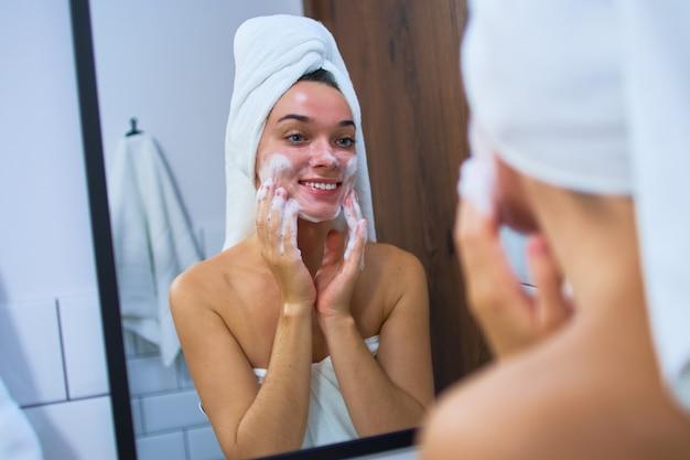 Jeune jolie femme souriante portant une serviette blanche se regardant au miroir de la salle de bain et se laver le visage avec de la mousse pour le visage après la douche