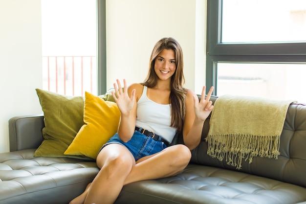 Jeune jolie femme souriante et à la recherche amicale, montrant le numéro huit ou huitième avec la main en avant, compte à rebours