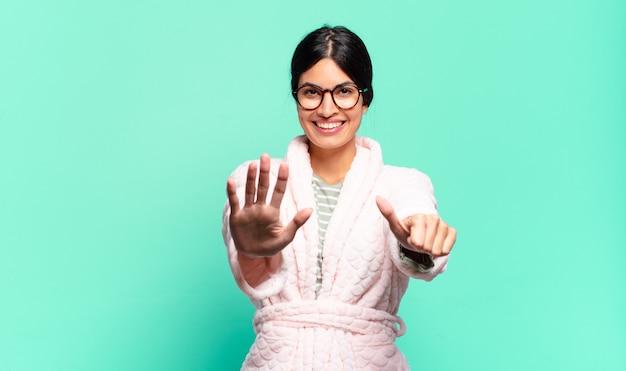 Jeune jolie femme souriante et à la recherche amicale, montrant le numéro six ou sixième avec la main en avant, compte à rebours. concept de pyjama