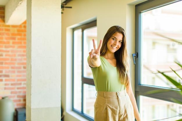 Jeune jolie femme souriante et à la recherche heureuse, insouciante et positive, gesticulant la victoire ou la paix d'une main