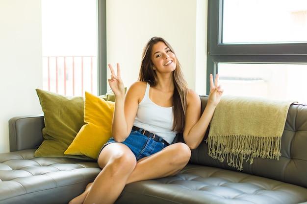 Jeune jolie femme souriante et à la recherche heureuse, sympathique et satisfaite, gesticulant la victoire ou la paix à deux mains