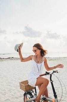 Jeune jolie femme souriante en robe blanche à cheval sur la plage tropicale à vélo portant chapeau et lunettes de soleil