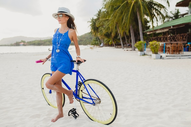 Jeune jolie femme souriante en robe bleue marchant sur la plage tropicale avec vélo portant chapeau et lunettes de soleil