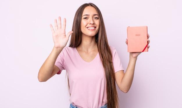 Jeune jolie femme souriante et semblant amicale, montrant le numéro cinq. concept de planificateur 2022