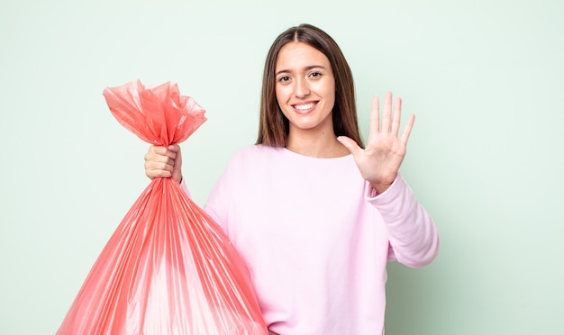 Jeune jolie femme souriante et semblant amicale, montrant le numéro cinq. notion de poubelle