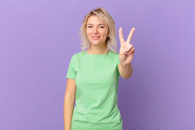 Jeune jolie femme souriante et semblant amicale, montrant le numéro deux