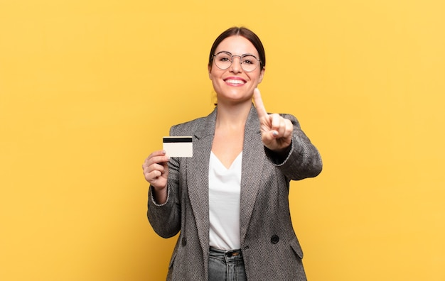 Jeune jolie femme souriante et semblant amicale, montrant le numéro un ou le premier avec la main en avant, comptant à rebours