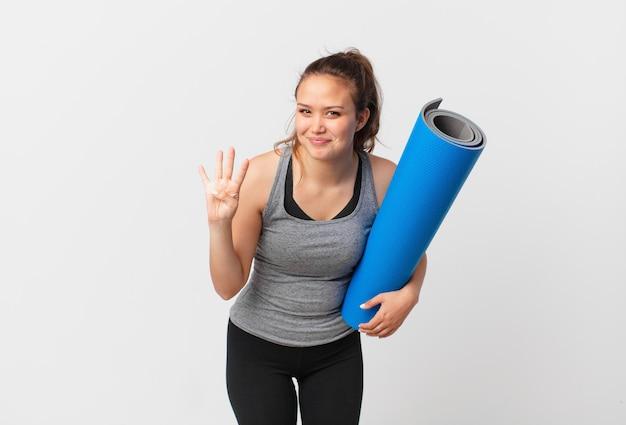 Jeune jolie femme souriante et semblant amicale, montrant le numéro quatre et tenant un tapis de yoga