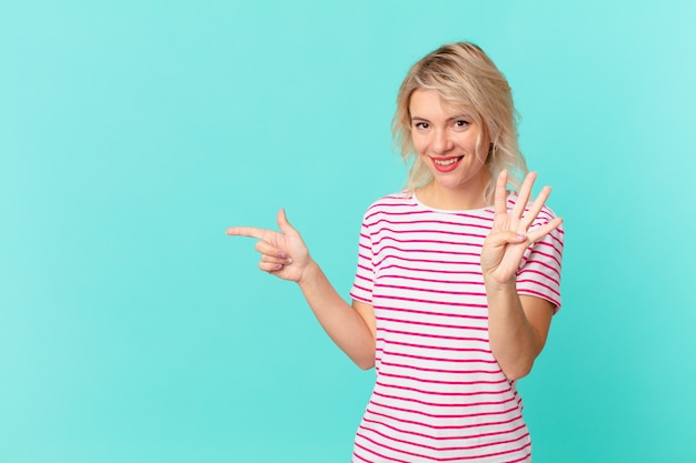 Jeune jolie femme souriante et semblant amicale, montrant le numéro quatre