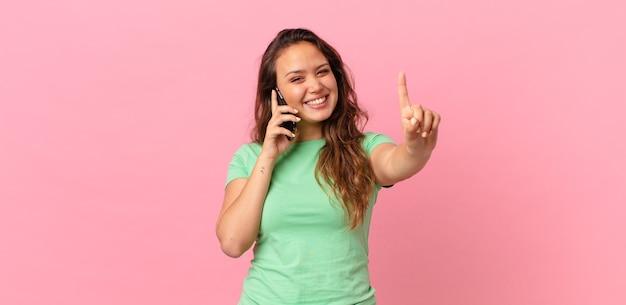 Jeune jolie femme souriante et semblant amicale, montrant le numéro un et tenant un téléphone intelligent