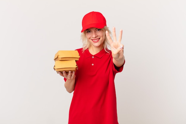 Jeune jolie femme souriante et semblant amicale, montrant le numéro trois. concept de livraison de hamburgers
