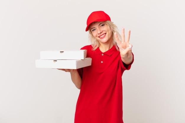 Jeune jolie femme souriante et semblant amicale, montrant le numéro trois. concept de livraison de pizza