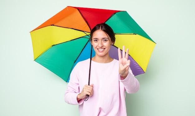 Jeune jolie femme souriante et semblant amicale, montrant le numéro trois. concept de parapluie