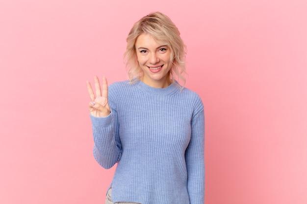 Jeune jolie femme souriante et semblant amicale, montrant le numéro trois