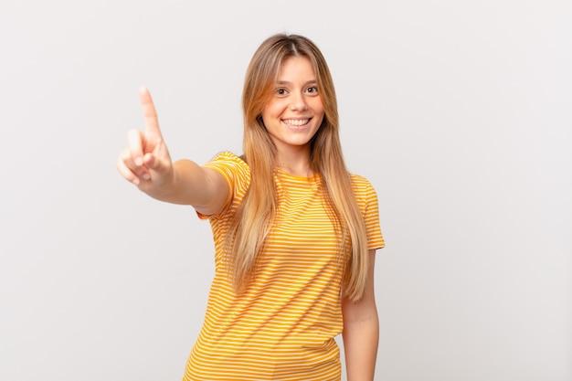 Jeune jolie femme souriante et semblant amicale, montrant le numéro un
