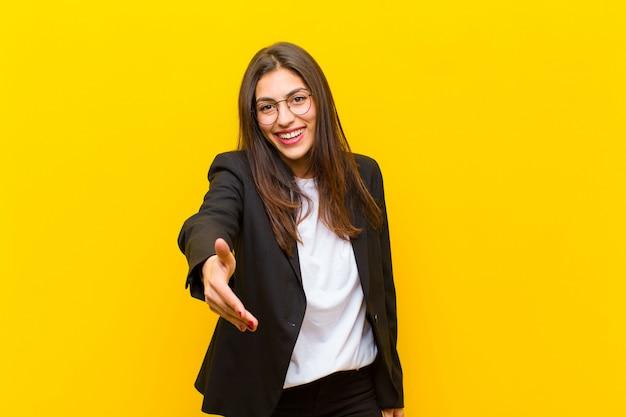 Jeune jolie femme souriante, semblant heureuse, confiante et amicale, offrant une poignée de main pour conclure un marché, coopérant contre le mur orange