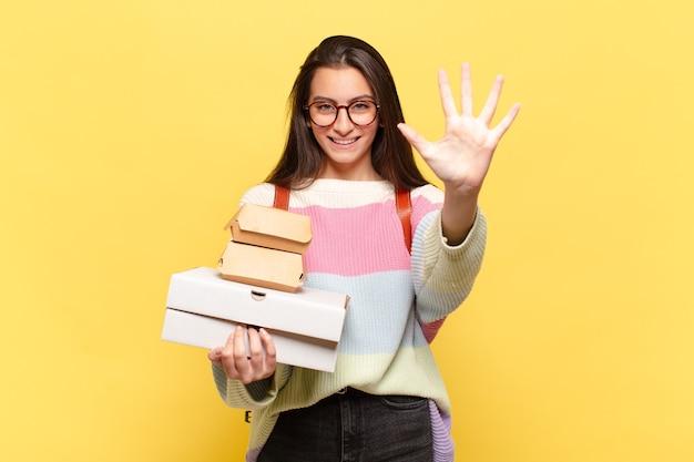 Jeune jolie femme souriante et à la sympathique, montrant le numéro cinq ou cinquième avec la main en avant, compte à rebours