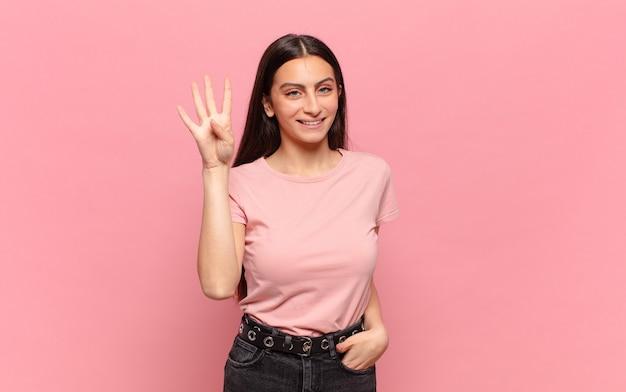 Jeune jolie femme souriante et à la sympathique, montrant le numéro quatre ou quatrième avec la main en avant, compte à rebours