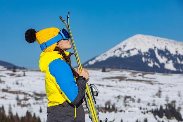 Jeune jolie femme souriante tenant le ski. montagnes en arrière-plan. voyage d'hiver. espace de copie