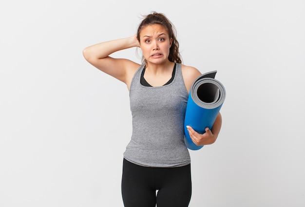 Jeune jolie femme stressée, anxieuse ou effrayée, les mains sur la tête et tenant un tapis de yoga