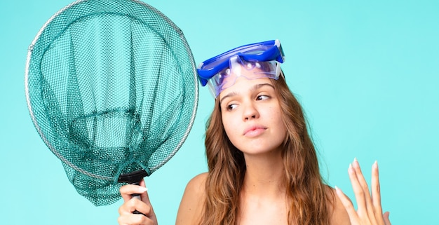 Jeune jolie femme stressée, anxieuse, fatiguée et frustrée par des lunettes et un filet de pêche