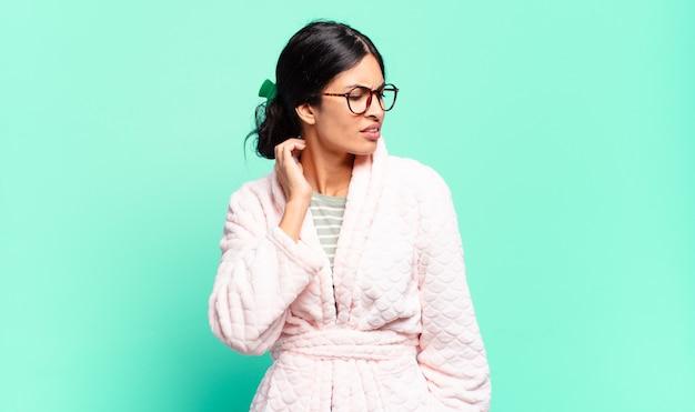 Jeune jolie femme stressée, frustrée et fatiguée, frottant le cou douloureux, avec un regard inquiet et troublé. concept de pyjama