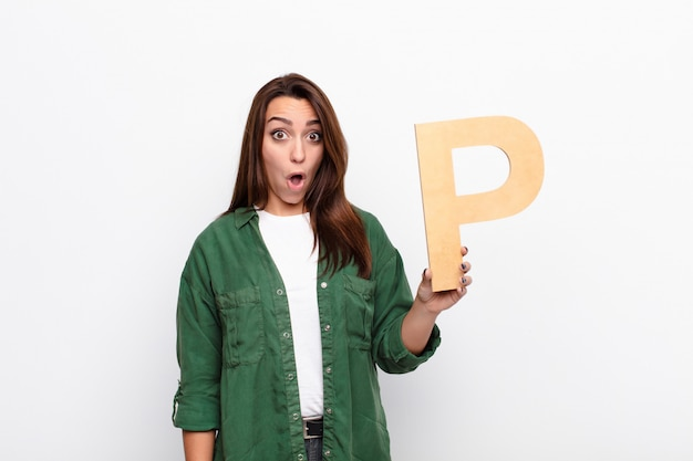 Jeune jolie femme surprise, choquée, émerveillée, tenant la lettre p
