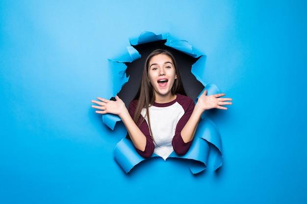 Jeune jolie femme surprise en regardant à travers le trou bleu dans le mur de papier.