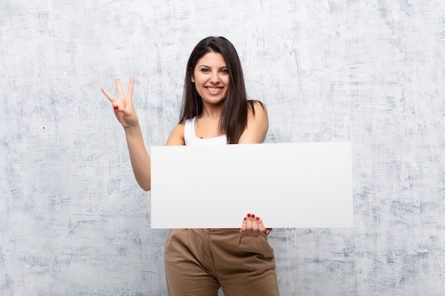 Jeune jolie femme tenant une bannière contre le mur de grunge