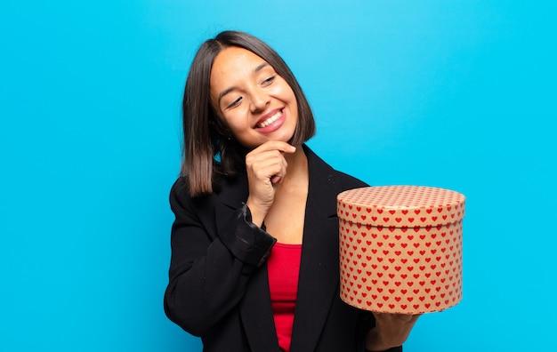 Jeune jolie femme tenant une boîte-cadeau