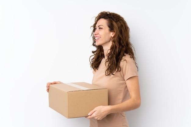 Jeune jolie femme tenant une boîte pour la déplacer sur un autre site