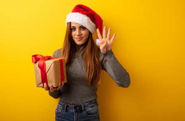 Jeune jolie femme tenant un cadeau montrant le numéro quatre