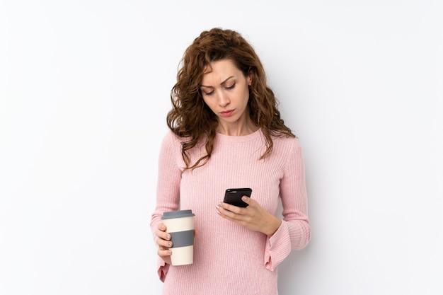 Jeune jolie femme tenant un café à emporter et un téléphone portable