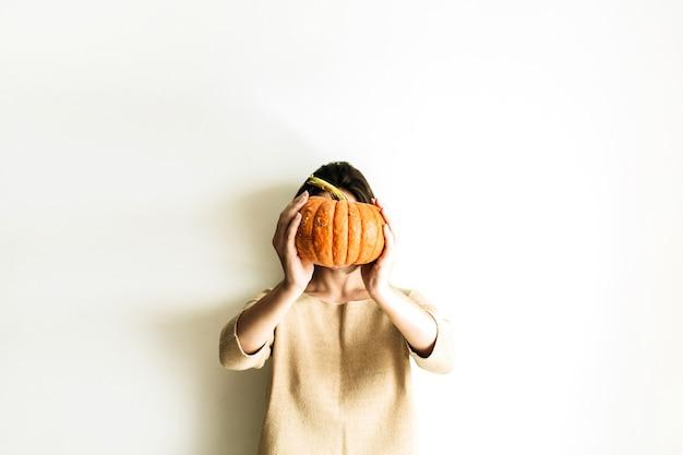 Jeune jolie femme tenant la citrouille d'halloween sur une surface blanche